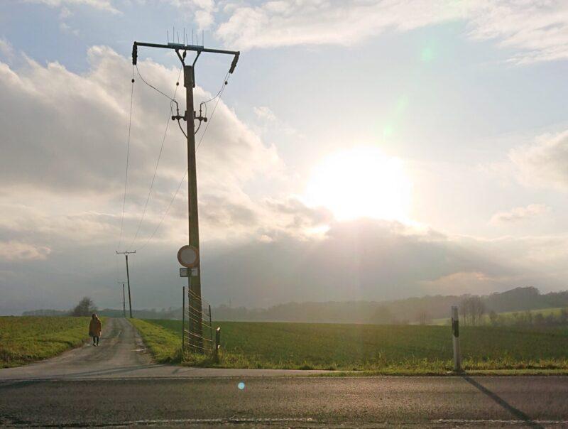 Sonnen hinter den Wolken, hügelige Landschaft, Straße